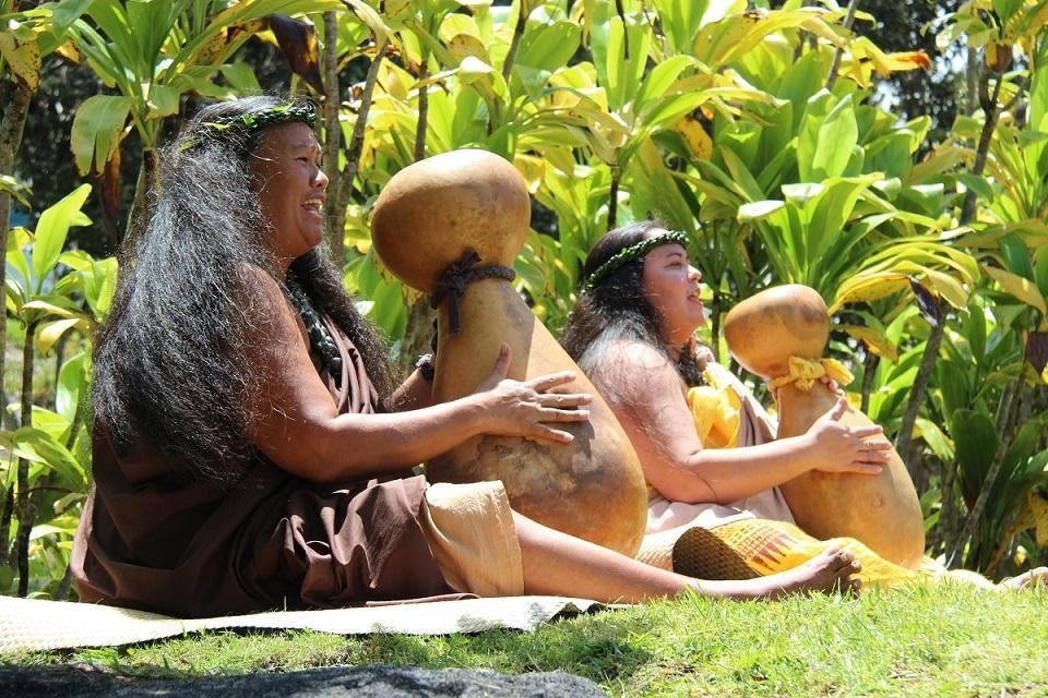 Cultural demonstrators sitting on grass at Hawaiʻi Volcanoes National Park Cultural Festival