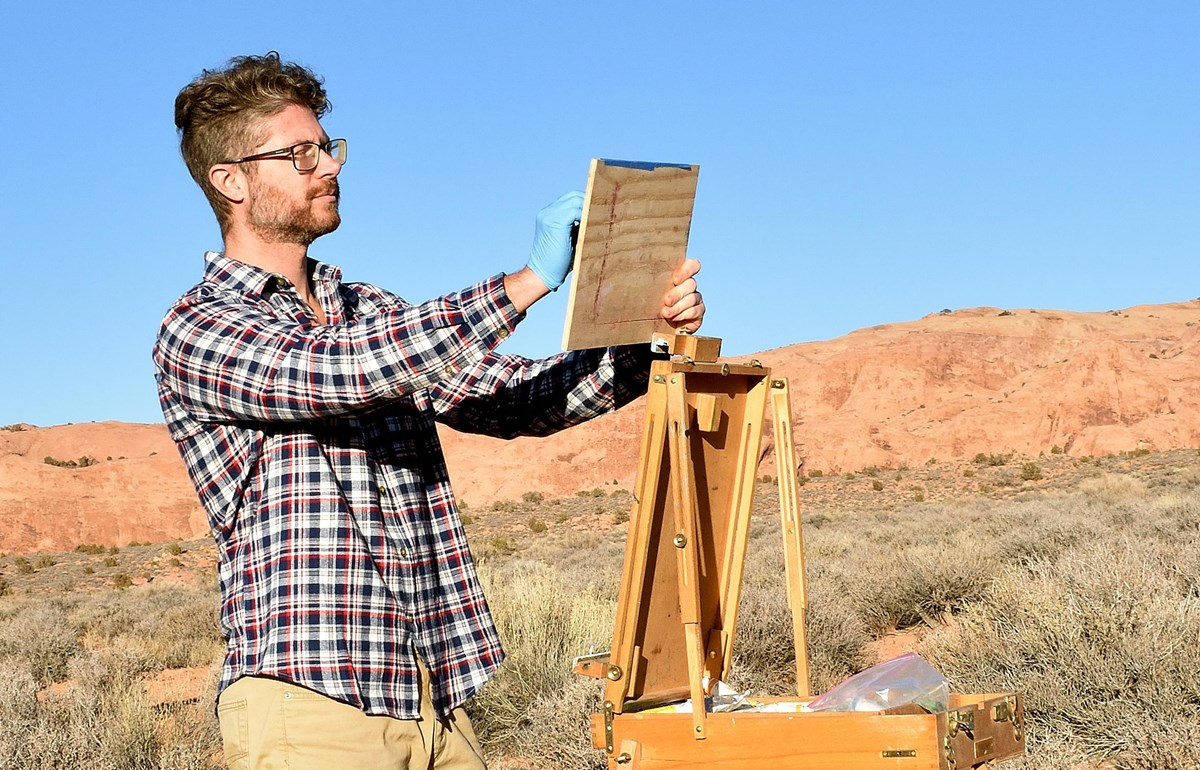 a man holds a wood board next to an easel