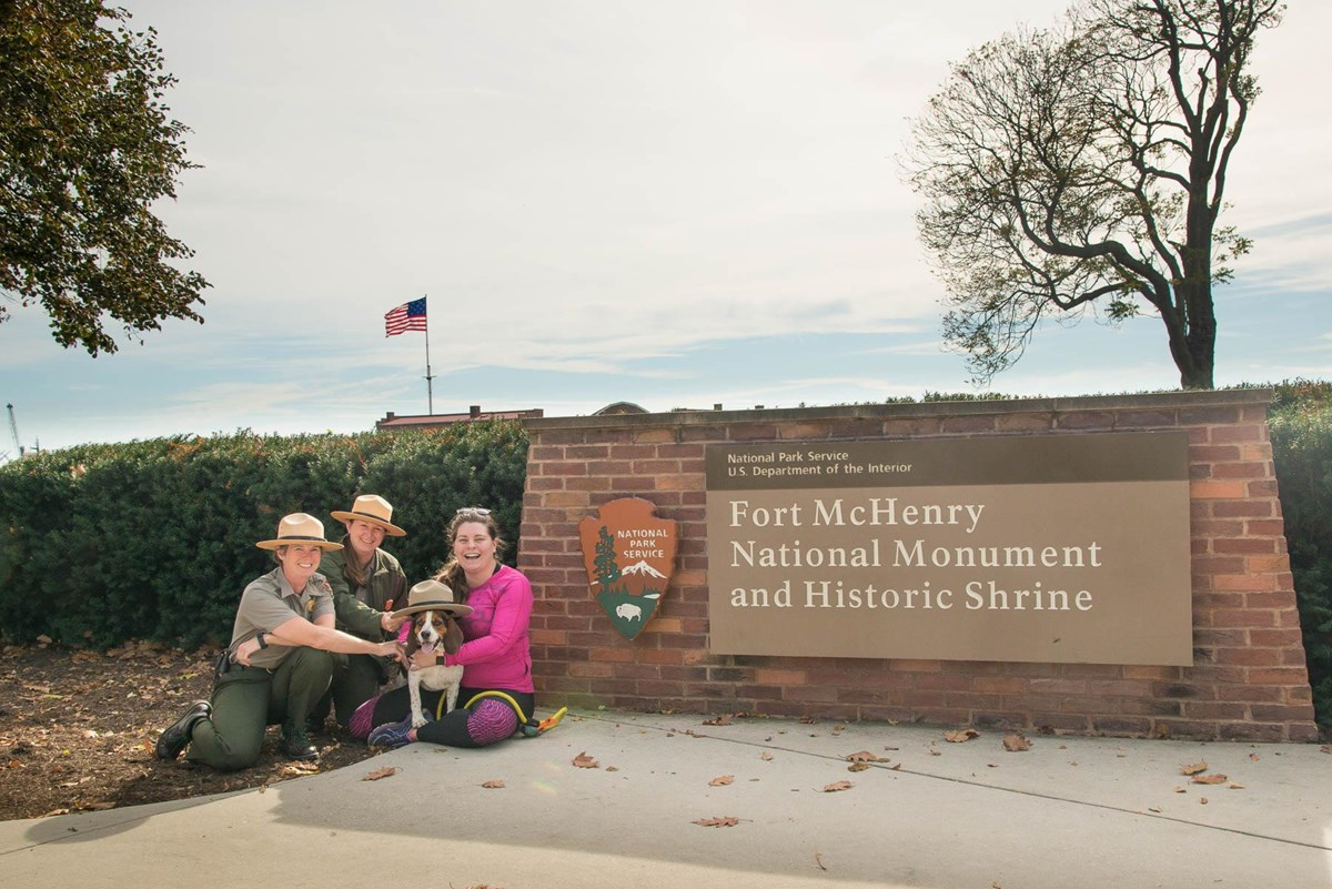 Park Rangers with visitor and dog in front of park sign.