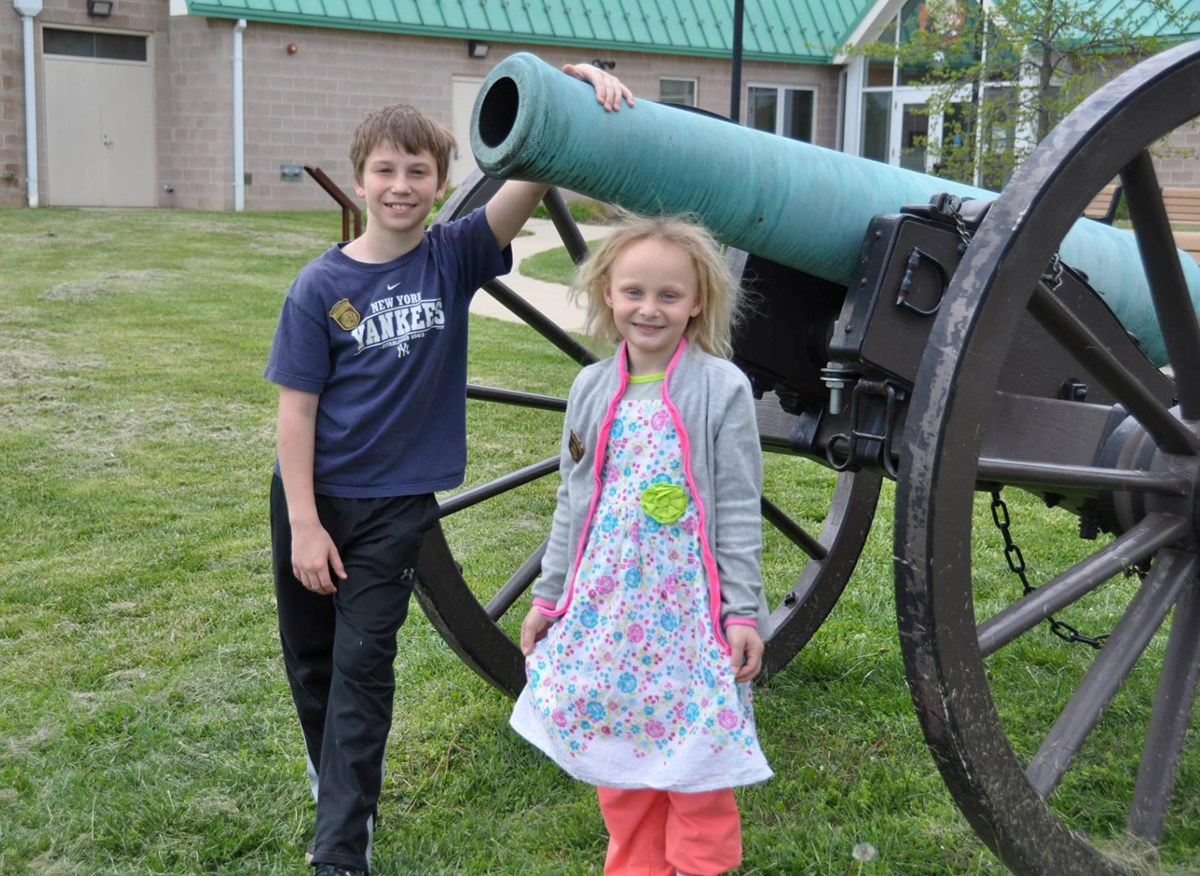 Two Junior Rangers standing beside a cannon