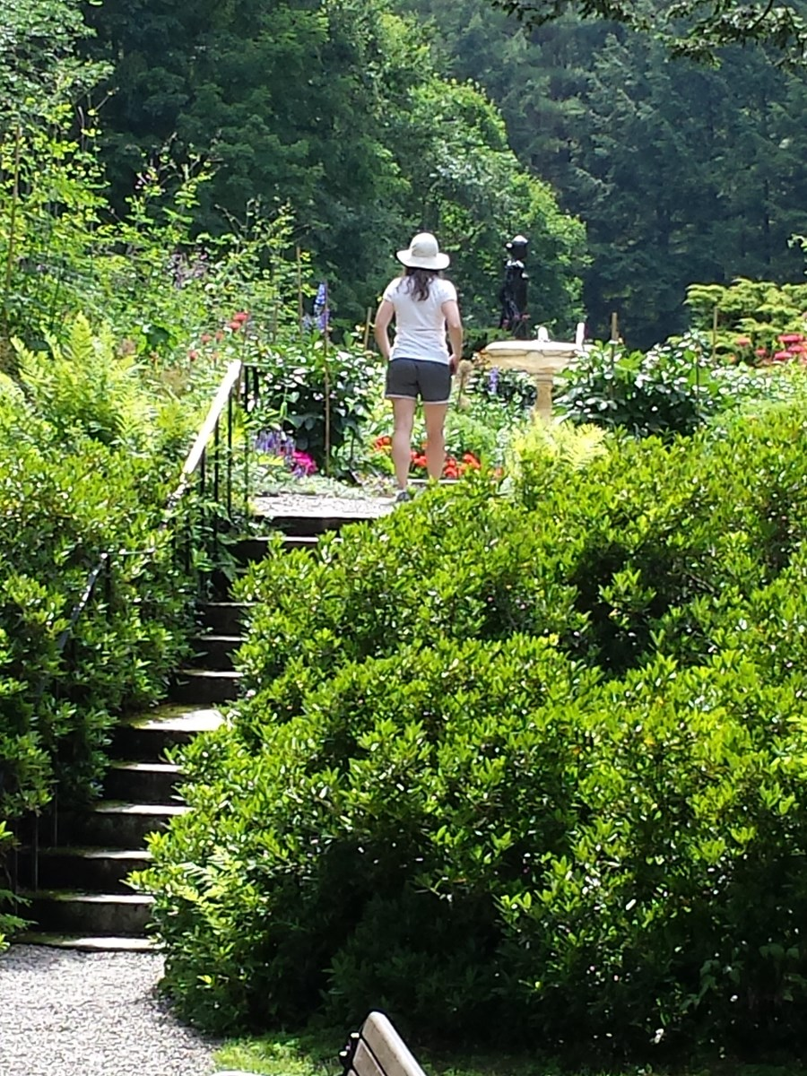 Visitor with hat in the formal gardens
