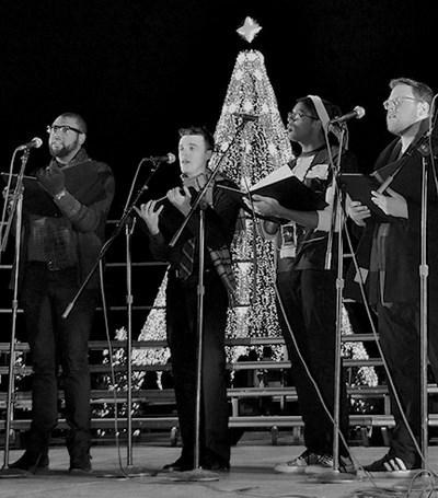 Singers perform in front of a Christmas tree