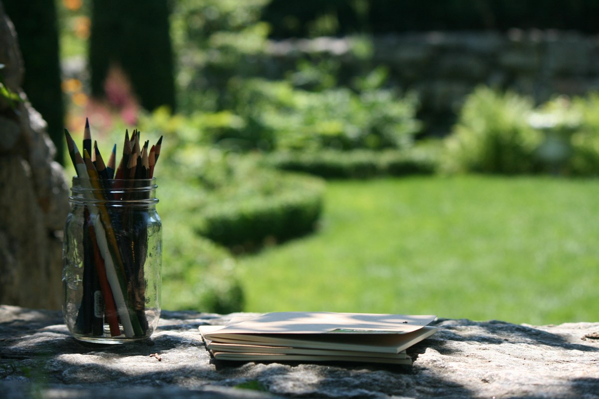 Colored pencils and journals rest on a stone wall with a garden in the background.