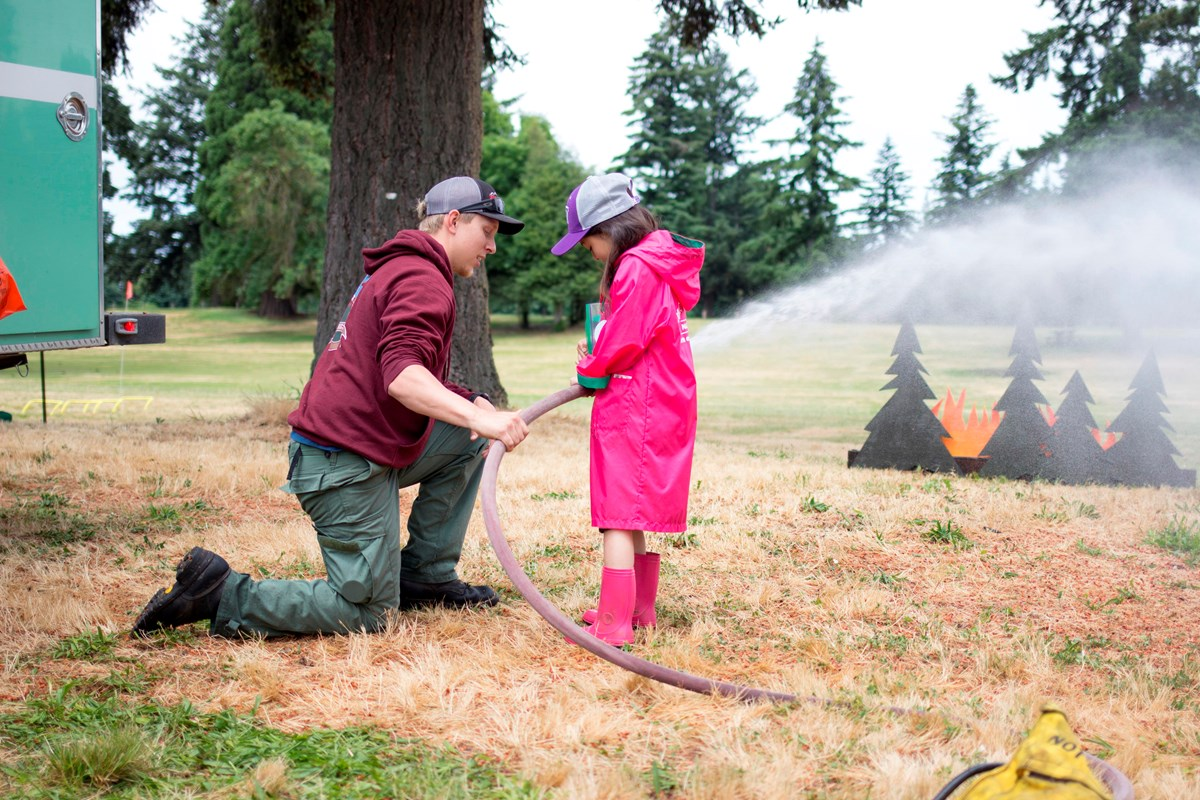 A firefighter kneels and shows a girl how to aim a hose at a pretend fire.