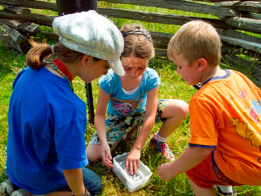 Three children open a geocache container at Piscataway Park along the Captain John Smith GeoTrail.