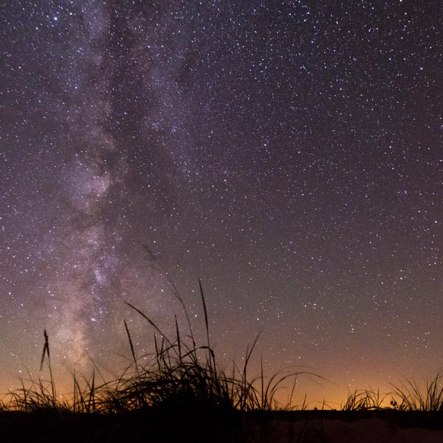Milky way glimmering above a dune.