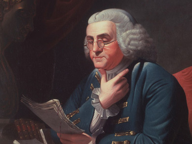 Color image of portrait of Ben Franklin, seated, wearing white wig and spectacles.