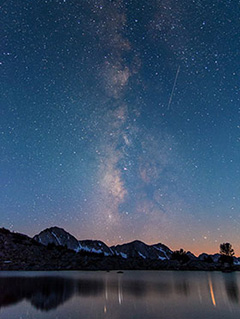 The Milky Way stretches from peaks along the horizon up into the sky