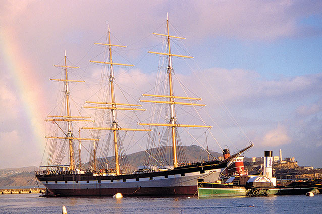 A full-rigged sailing ship with a rainbow behind it.