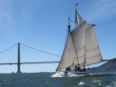 A scow schooner sailing on San Francisco Bay with the Golden Gate Bridge in the background.