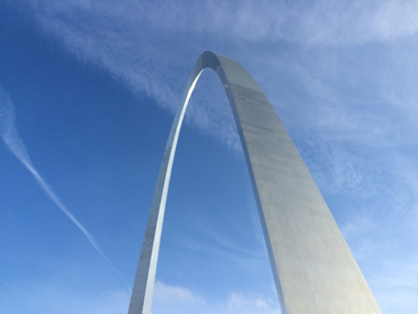 The Gateway Arch against a blue sky with clouds