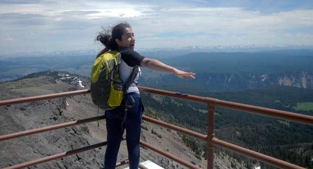 A young woman wearing a backpack stands on top of a windy lookout