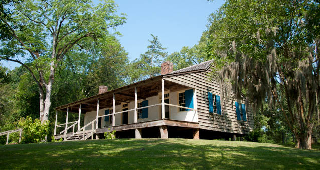A one-story plantation house with porch surrounded by trees, green foliage, and Spanish moss