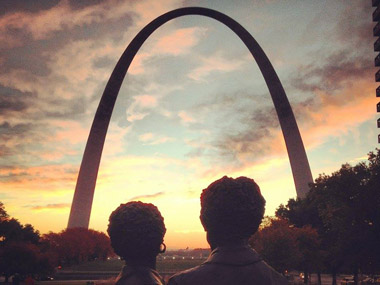Silhouette of the statue of Dred and Harriet Scott in front of the Gateway Arch at sunrise