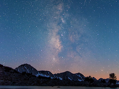 A very starry night sky over a row of peaks.