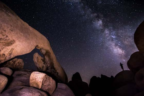 night scene showing the Milky Way galaxy over rock formations