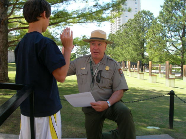 A child being sworn in as a Junior Ranger, by a National Park Service Ranger.