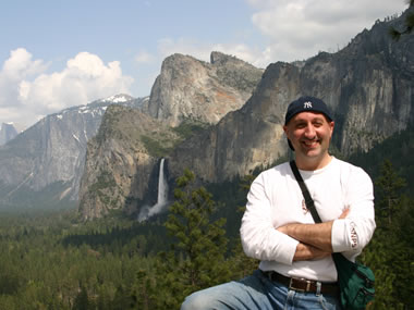 A park visitor stands in Yosemite Valley. Behind him is Yosemite Falls.