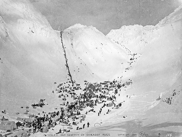 Historical photo of hundreds of people lined up to ascend a mountain pass.