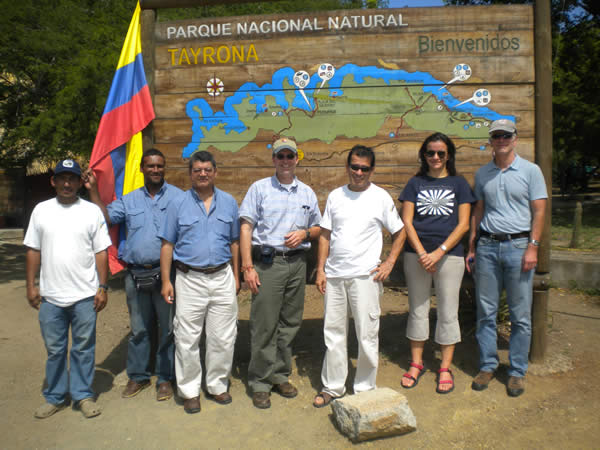 A group of friends stand in front of the Tayrona National Park sign in Colombia.