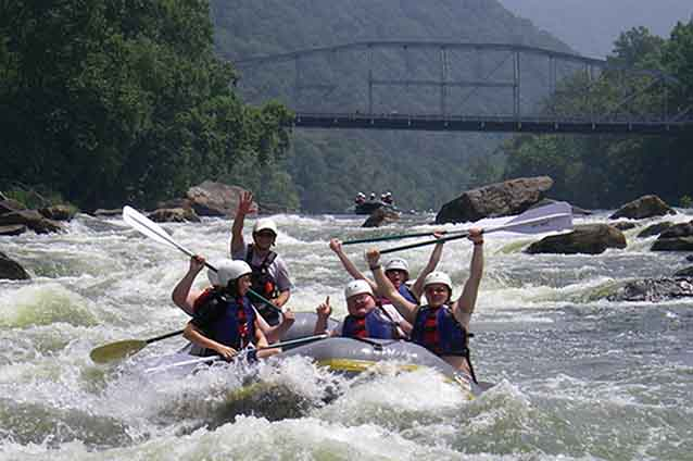 A raft coming through whitewater rapids on the Lower New River with a bridge in the background.