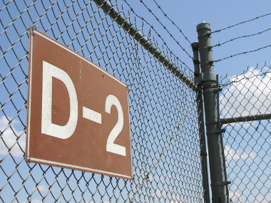 A security fence bearing a brown identifying sign.