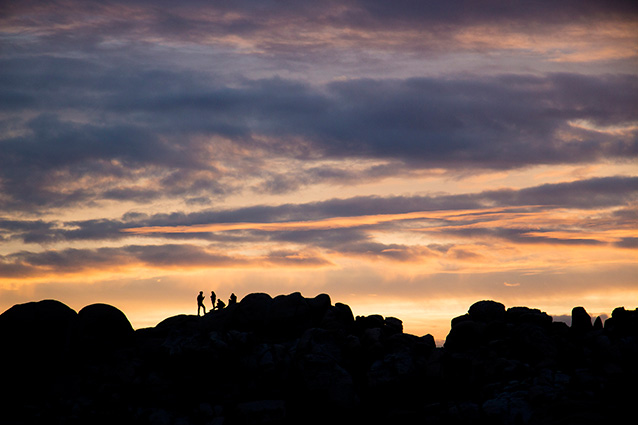 visitors silhouetted against the sunset at Jumbo Rocks campground
