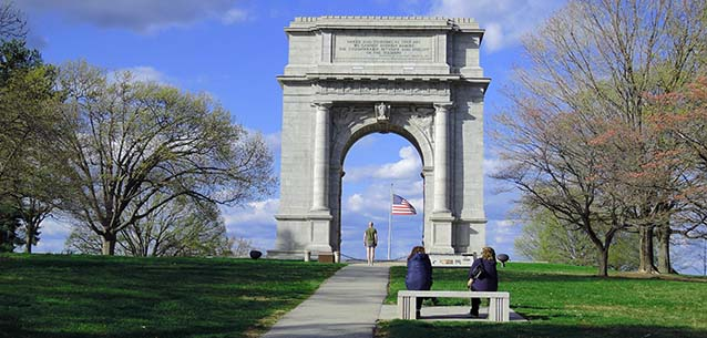 A runner stands under the towering National Memorial Arch in Valley Forge.