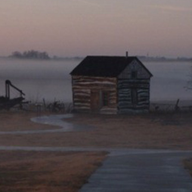 The Palmer-Epard Cabin rests at the end of the sidewalk with a hazy fog in the background.