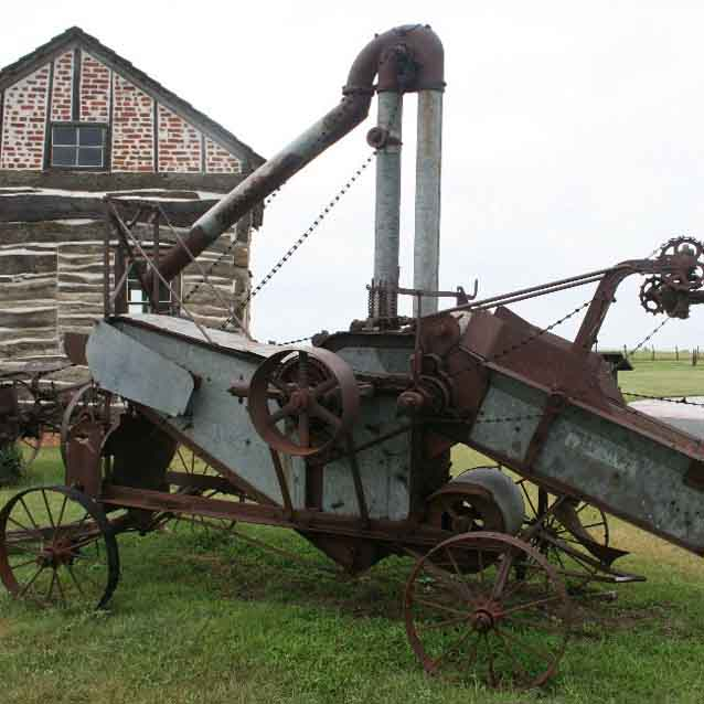 A farm implement rests in the grass by a homesteading cabin