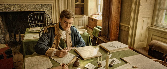 A Revolutionary War officer sitting at a desk writing letters.