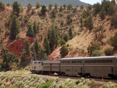 An Amtrak passenger train rounds the bend in a canyon.