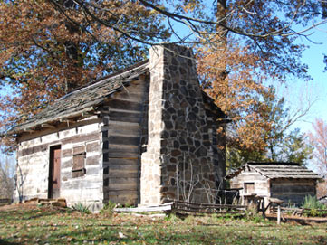 Replica Log Cabin surrounded by trees changing colors in the fall.