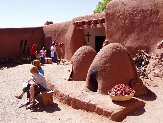 Alt text: adobe village with children and adults and chiles