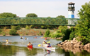 canoes and kayaks on the Mississippi River passing the Boom Island lighthouse