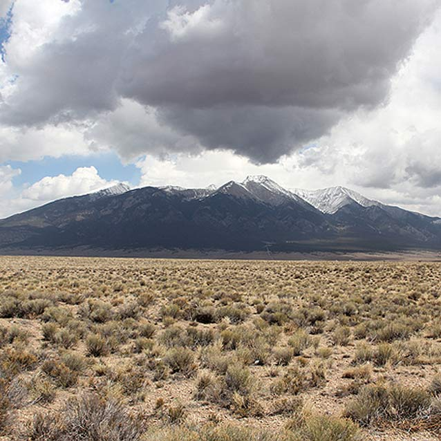 desert scrub in the foreground, spiky mountain range in the background with white clouds