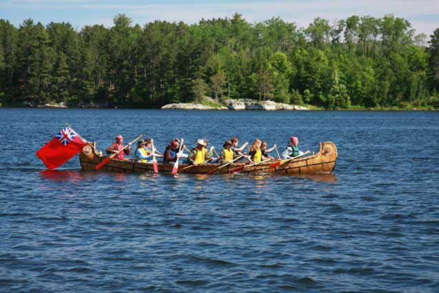 People paddling a replica North Canoe.