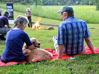 Two visitors and dog on blanket with ranger and campfire in background