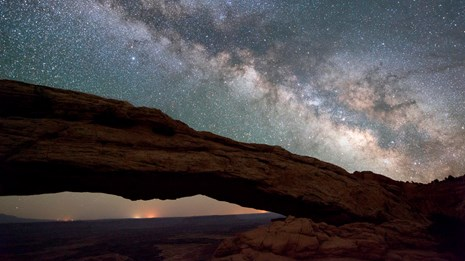 A natural arch formation frames this view of the Milky Way and constellations at Canyonlands NP