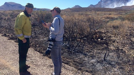 Big Bend NP employee talking to the media about a wildfire in the distance.