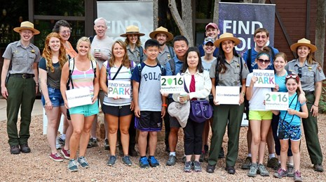 Group of park rangers and visitors with Find Your Park signs