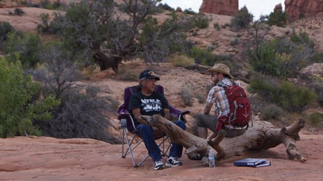 Two men sit, one in a chair and one on a log, in a desert area.