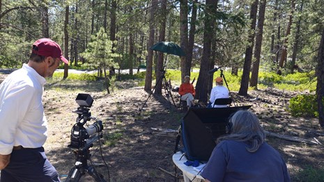 Two people film another interview a tribal member in a wooded area.
