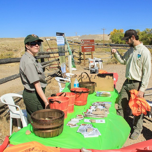 A NPS employee and a BLM employee standing next to a table with a brown national historic trail sign