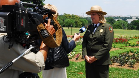 An NPS official speaks to a reporter and cameraman.