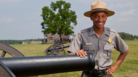 A ranger poses by a Civil War cannon.