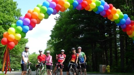 A group of bicyclists under a banner of rainbow balloons.