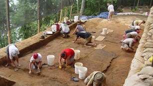 Team of Archeologists excavate unit