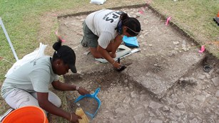 Archeologists trowel excavation unit
