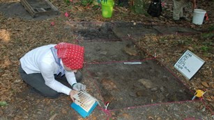 Volunteer using Munsell color book to record description of soil